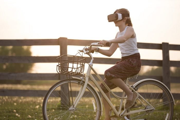 girl-rides-a-bike-wearing-hmd-and-watching-vr-content