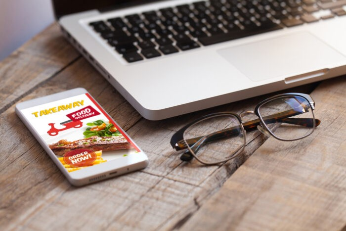 notebook-glasses-and-phone-with-food-delivery-app-on-the-screen